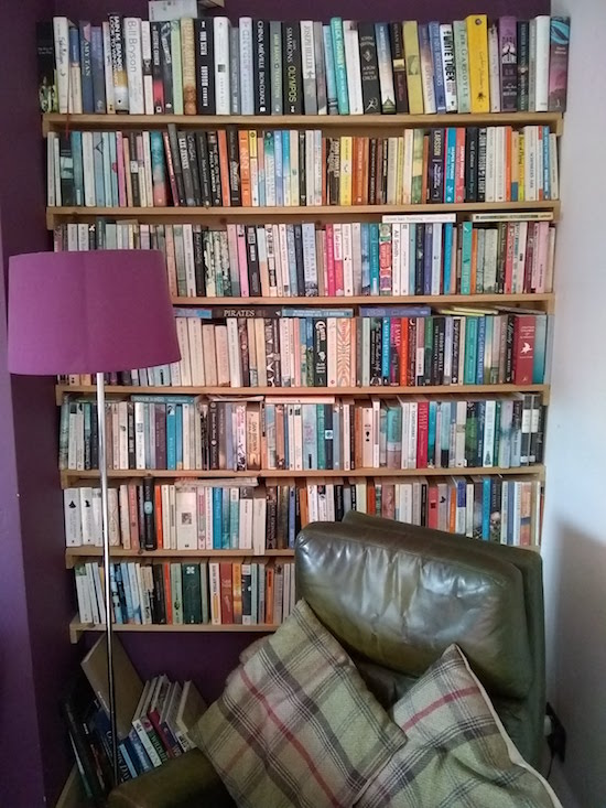Photo of a crowded bookshelf with a cozy chair in front of it.