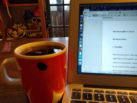 Photo of a cup of tea beside a computer screen in which the document's title is revealed as THIS DOWNFALL.