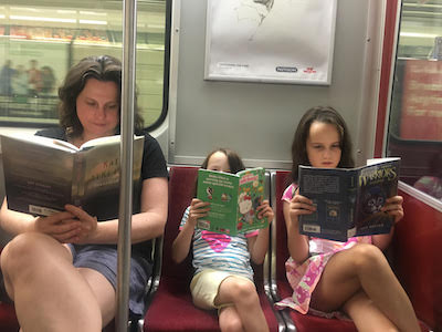 A woman and two children riding the subway, all reading books.