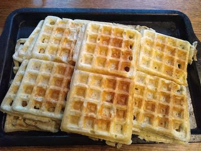 A baking pan heaped with waffles. Photograph.