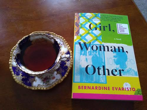 Photo of a cup of tea (in a fancy cup with saucer) on a table beside GIRL WOMAN OTHER by Bernardine Evaristo.