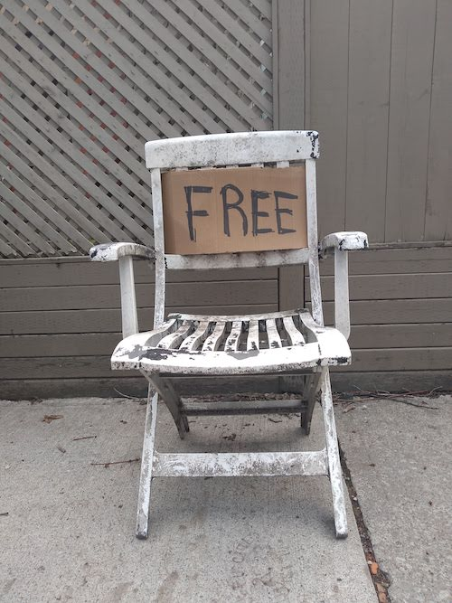 Image of a battered old plastic chair sitting on the sidewalk with a handwritten cardboard sign on it saying FREE.