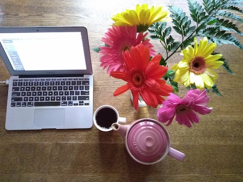 A desktop with a laptop computer, bouquet of daisies, and a pink teapot.